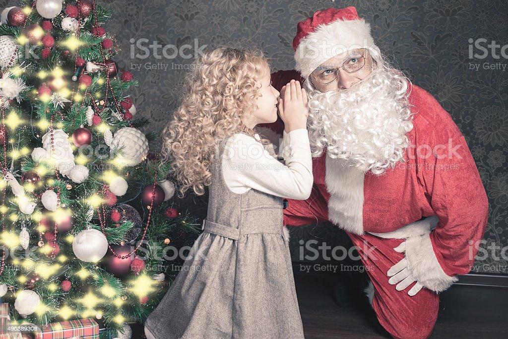 Little girl talk to Santa Claus wishlist, gifts, Christmas night stock photo