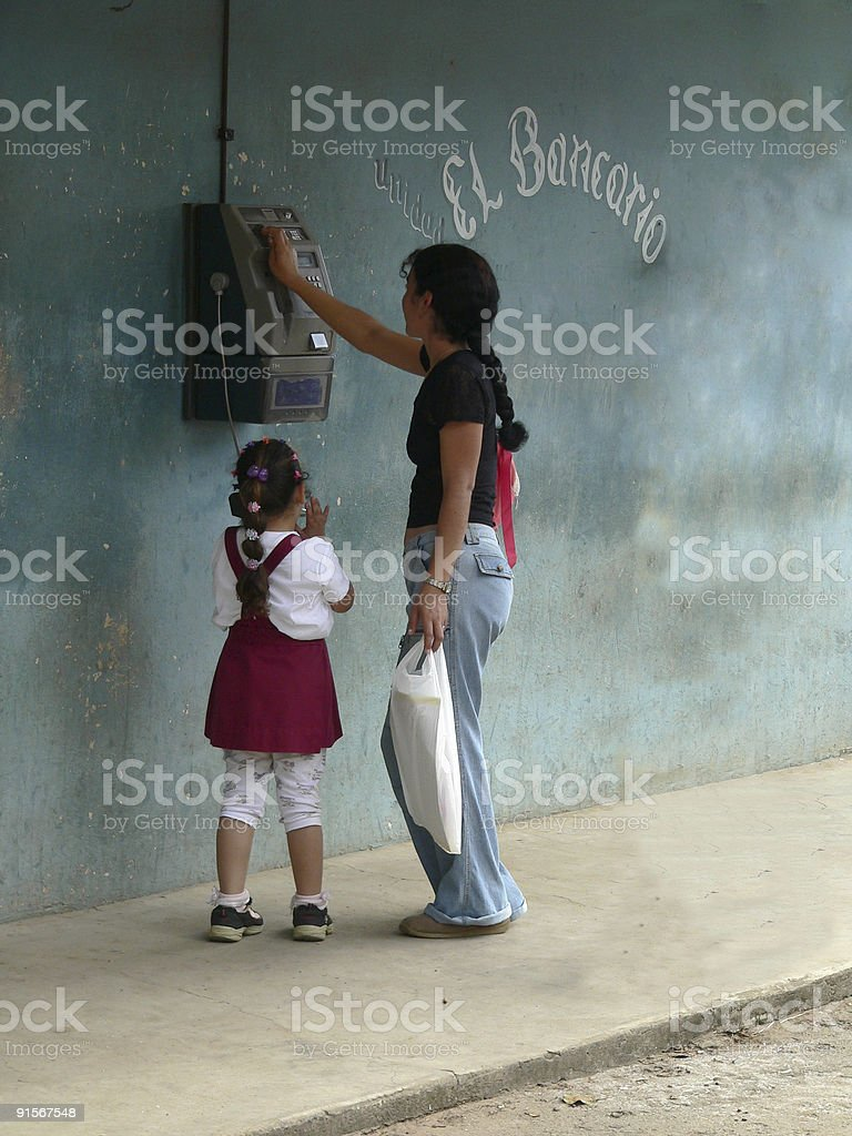 Little girl talking on a public payphone in Vinales Cuba royalty-free stock photo