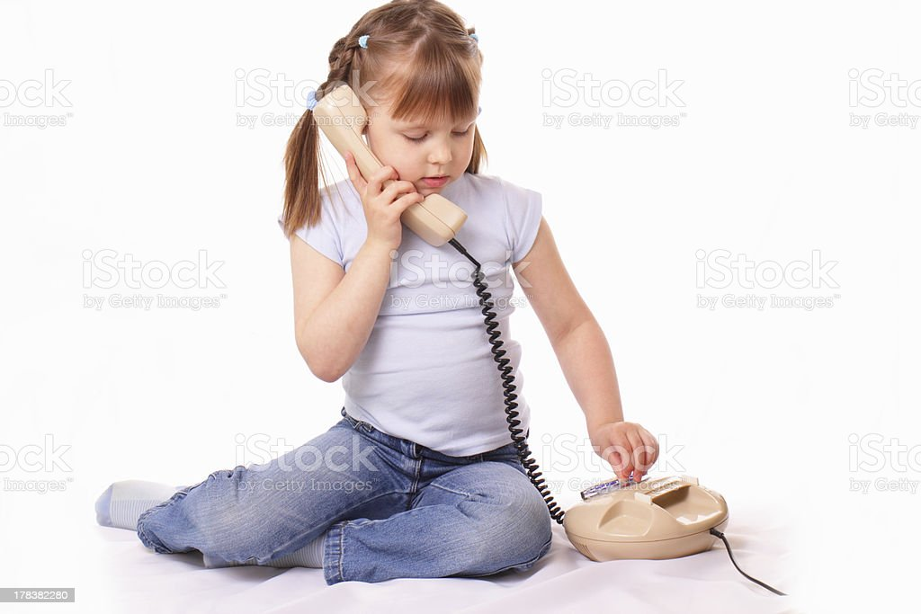 Little girl talking on the old phone stock photo