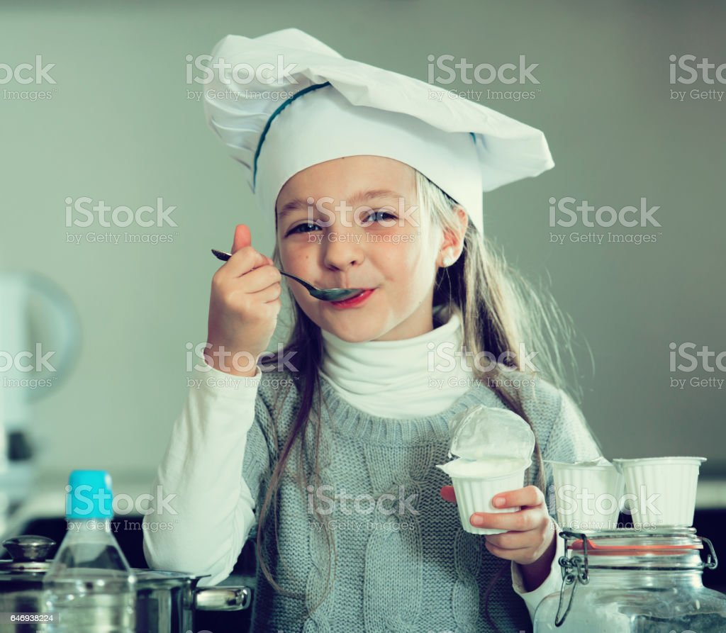Little girl tasting fresh yoghurt in kitchen and smiling stock photo