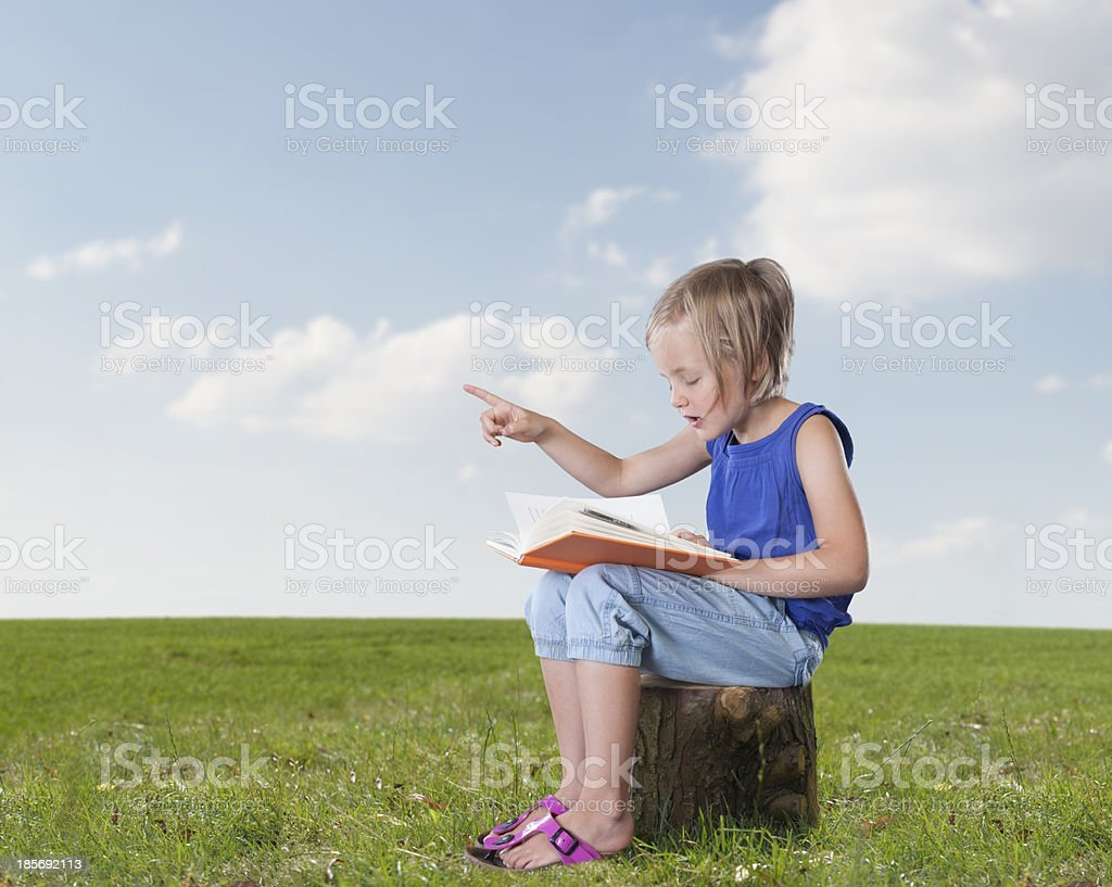 little girl telling a story, outdoors stock photo