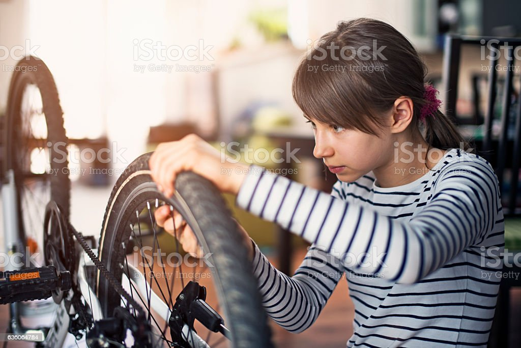 Little girl tending to her bicycle at home stock photo