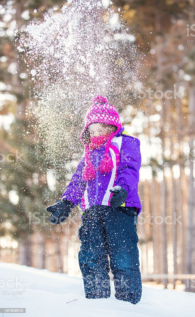 Little Girl Throwing Handful of Snow Into Air stock photo