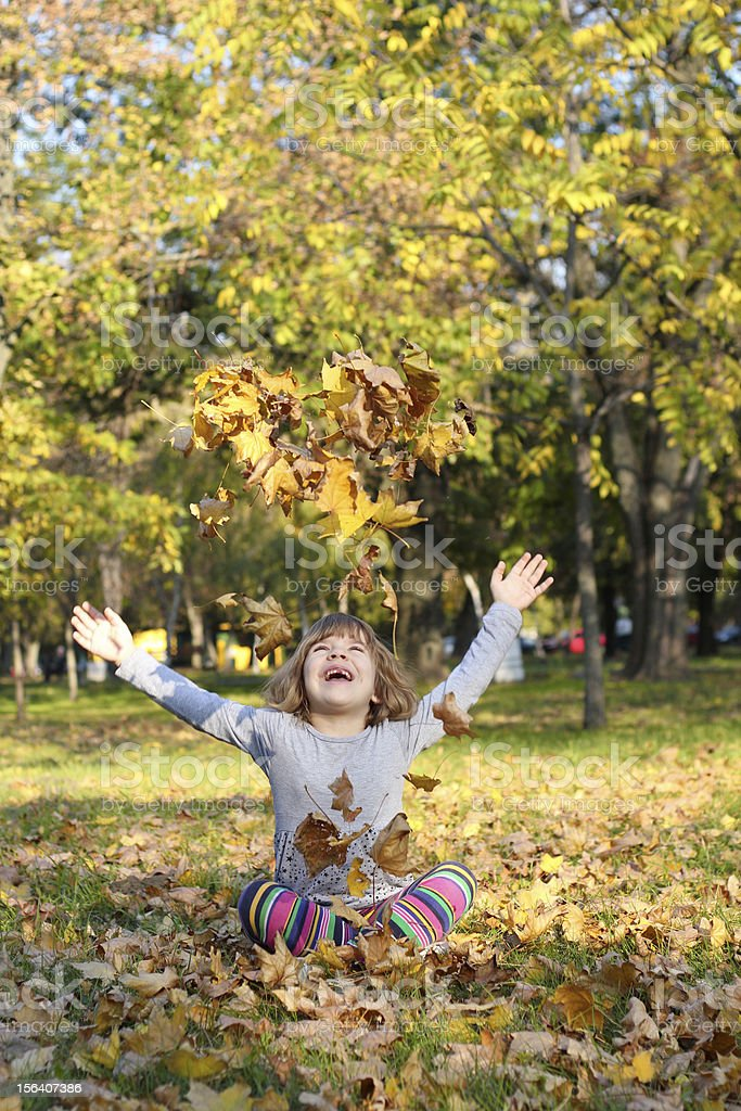 little girl throws autumn leaves royalty-free stock photo