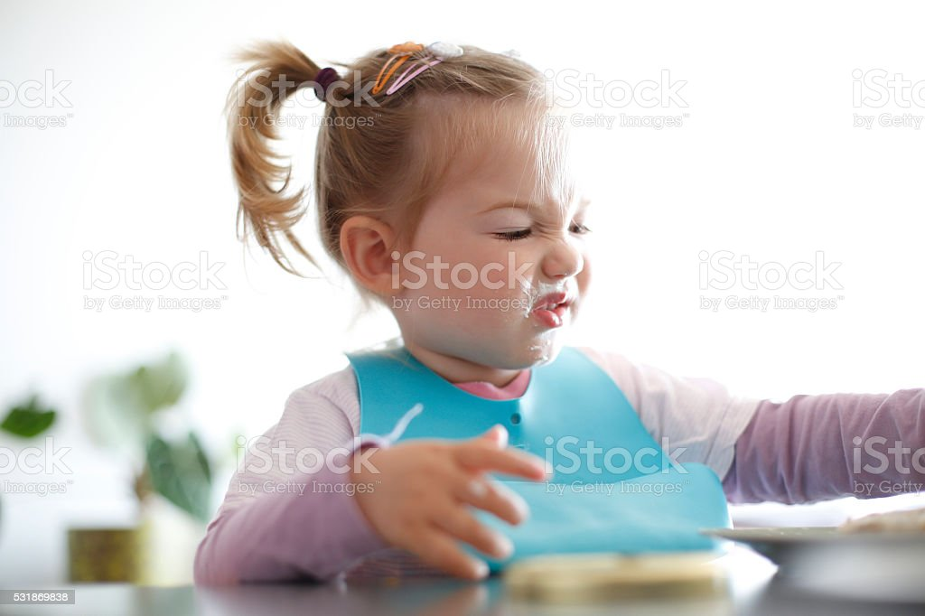 Little girl toddler picking her food, making faces stock photo