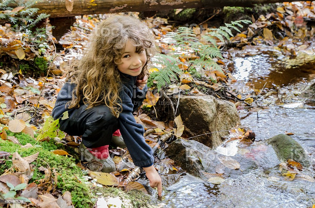 Little girl touching cold water of small river stock photo