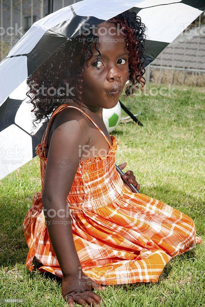 Little girl under umbrella stock photo