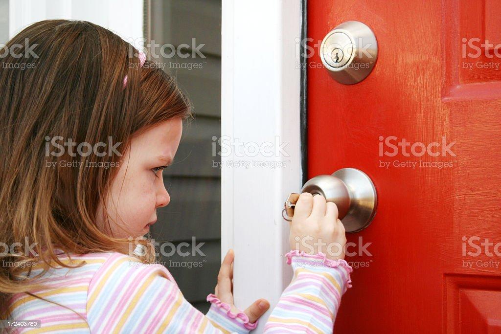 Little girl unlocking a red door stock photo