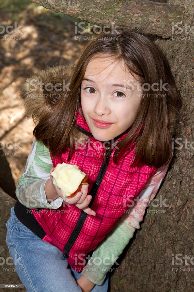 Little girl up a live oak tree with her apple. stock photo