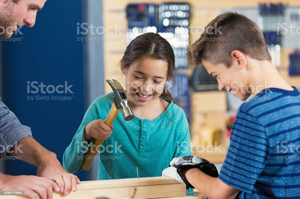 Little girl uses hammer in daycamp at local makerspace stock photo