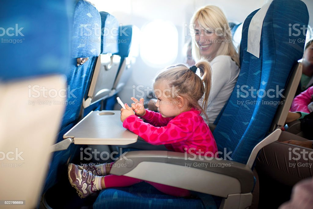 Little girl using cell phone in airplane. stock photo