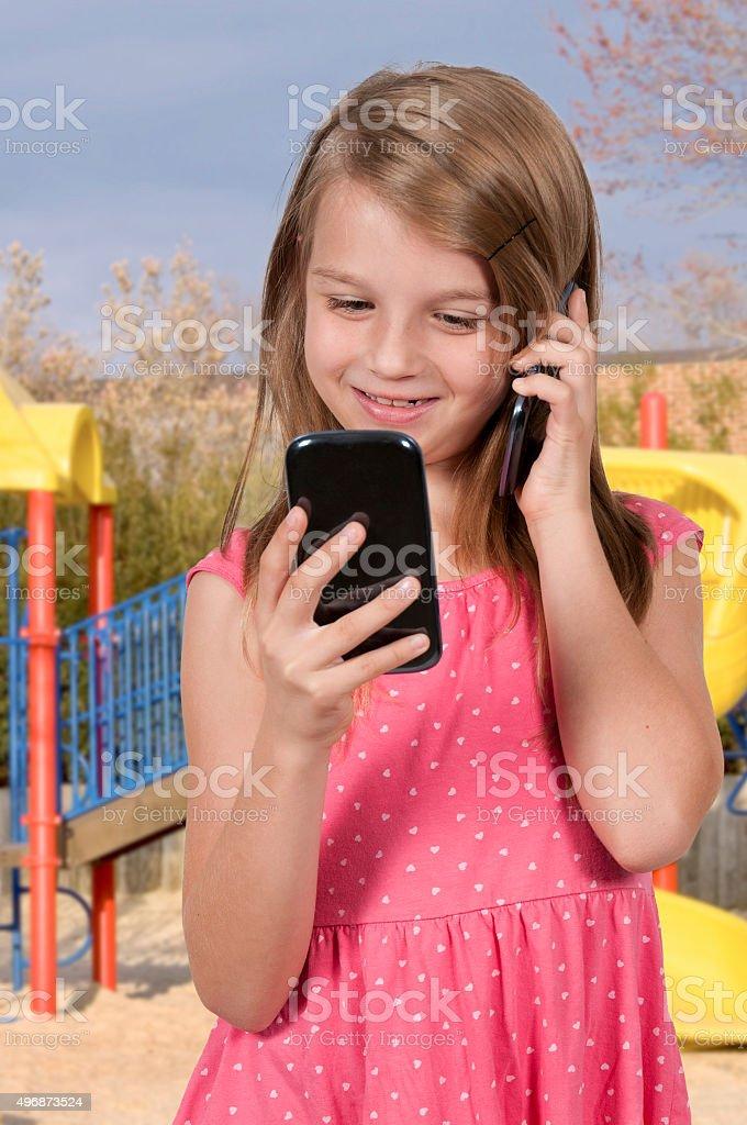 Little Girl Using Cell Phones stock photo