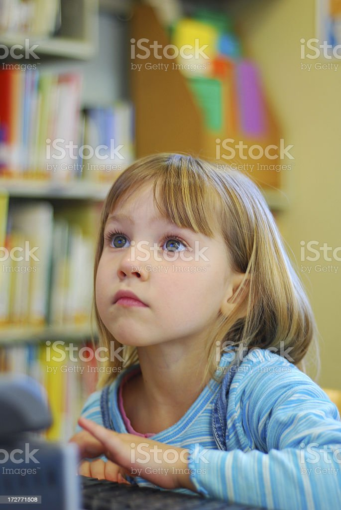 Little girl using computer in library royalty-free stock photo