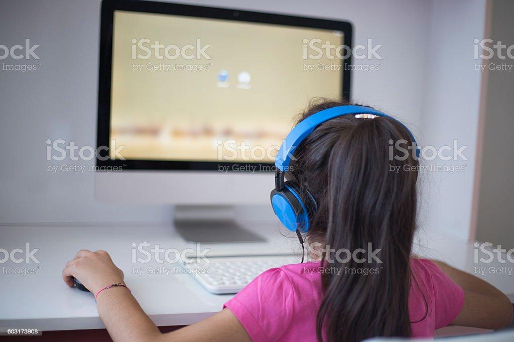 Little girl using computer stock photo