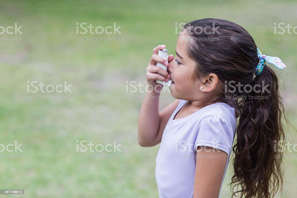 Little girl using his inhaler stock photo