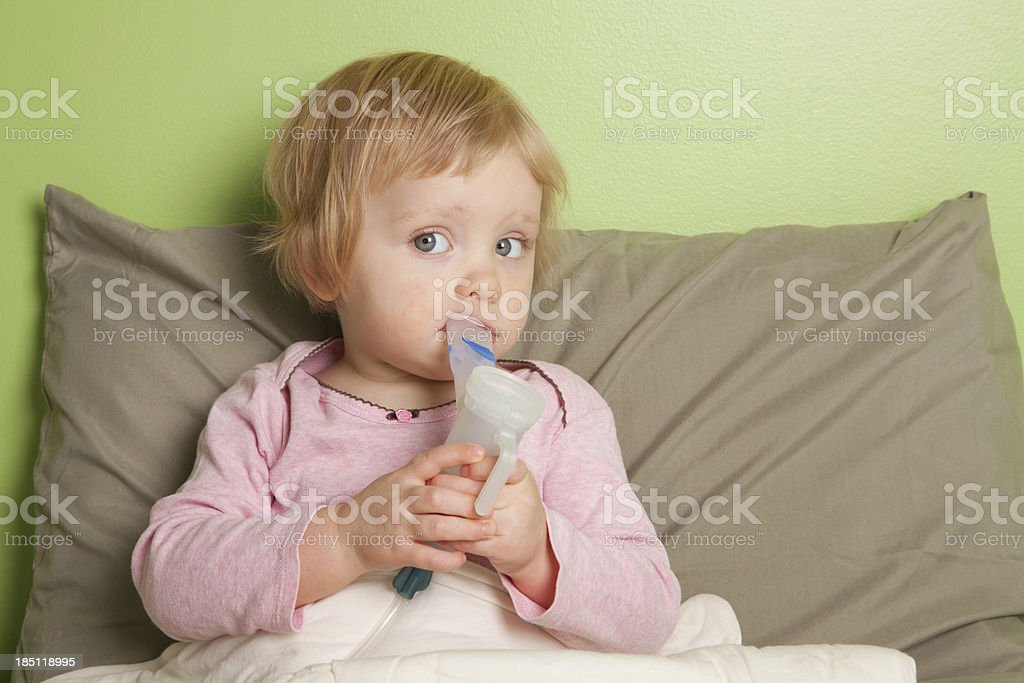 Little girl using inhaler / nebulizer stock photo