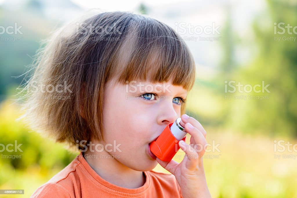 Little girl using inhaler on a sunny day stock photo