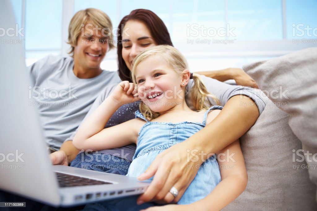 Little girl using laptop with young parents royalty-free stock photo