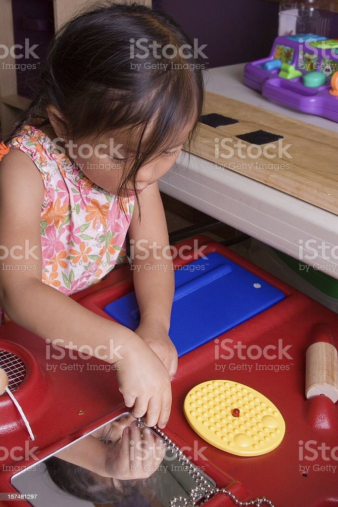Little girl using sensory station during therapy royalty-free stock photo