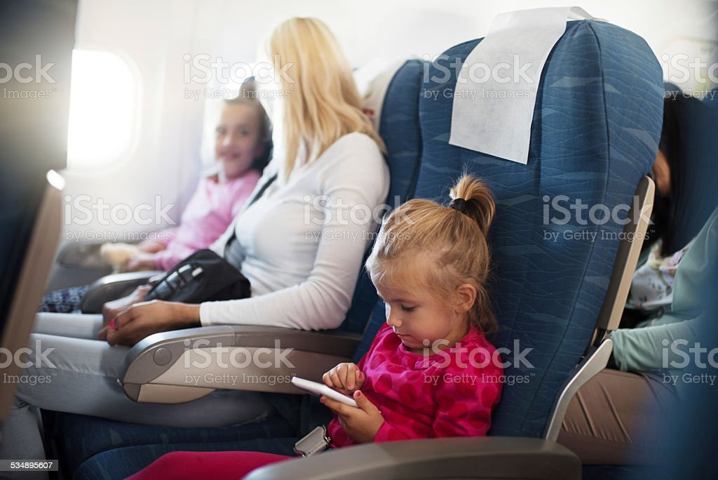 Little girl using smart phone in airplane. stock photo