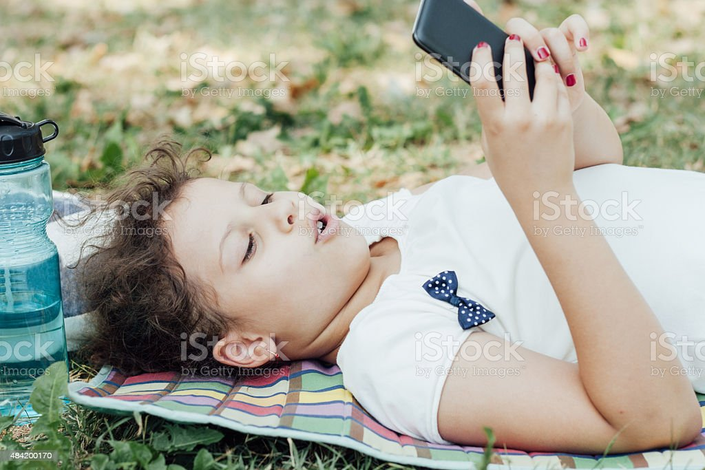 Little girl using smart phone stock photo
