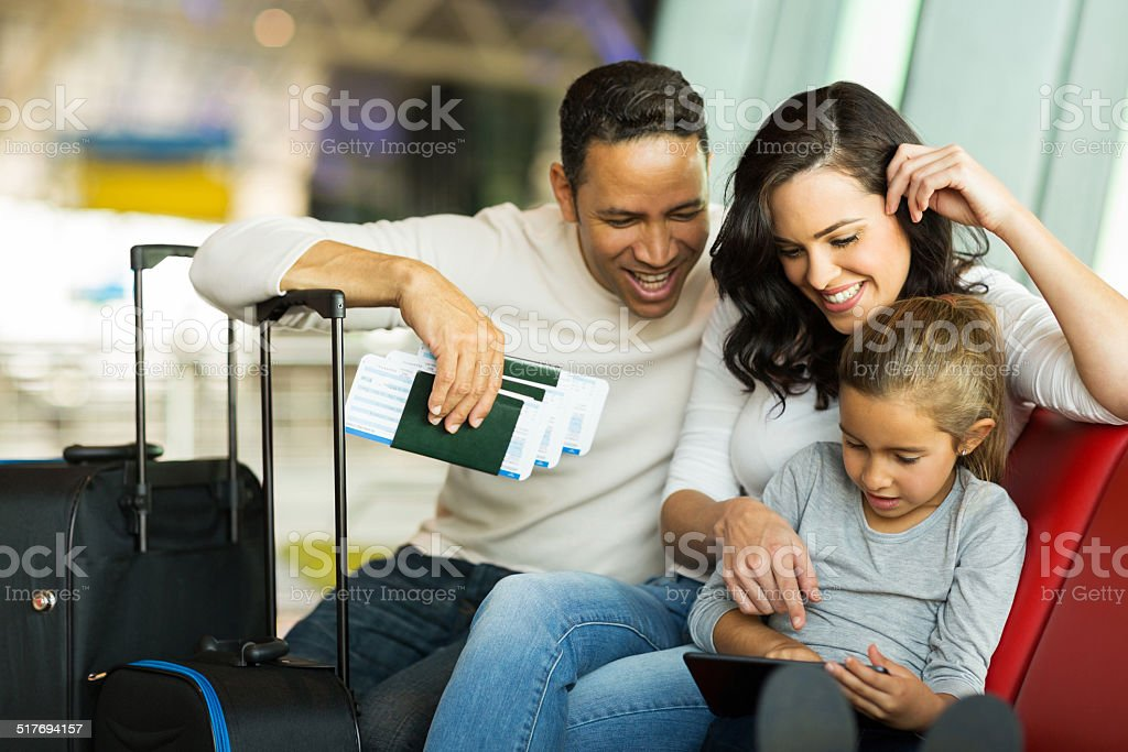 little girl using tablet pc with parents at airport stock photo