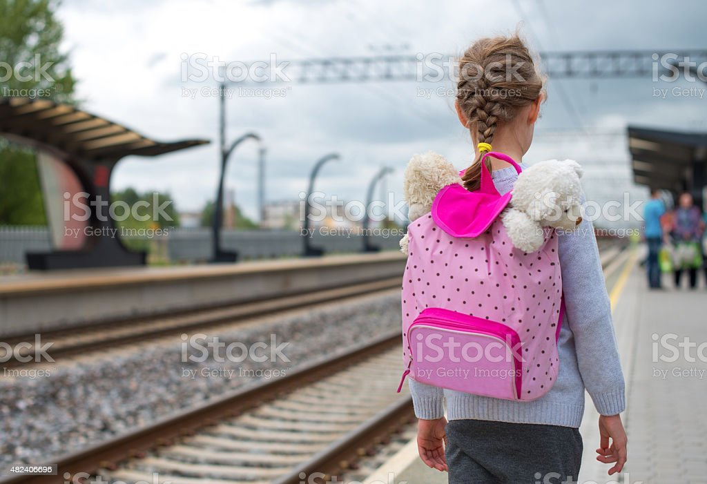Little girl waiting for train at the railway station. stock photo