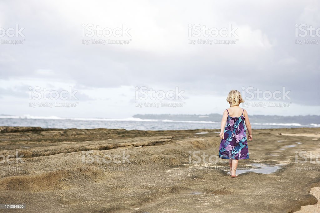 Little girl walking along the beach stock photo
