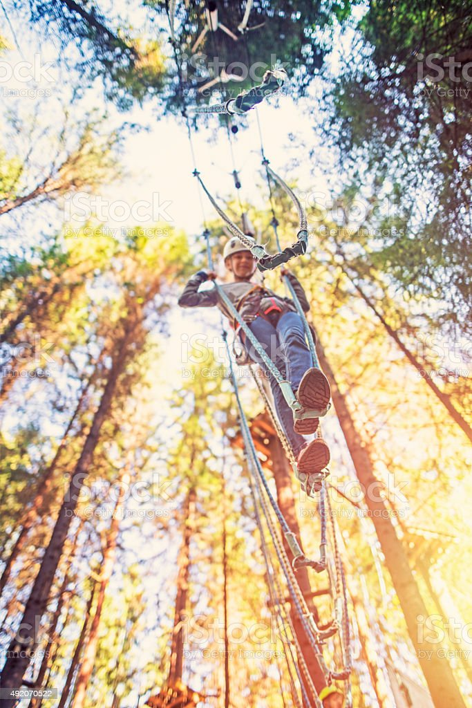 Little girl walking in ropes course adventure park stock photo