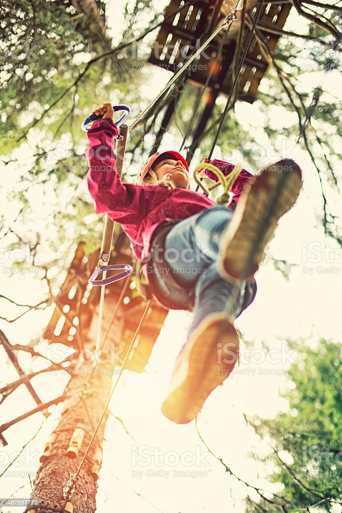 Little girl walking on a line in adventure park stock photo