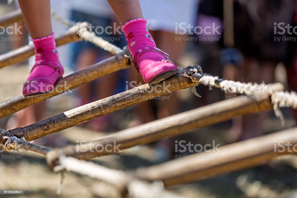 Little girl walking on rope-ladder at outdoor playset stock photo