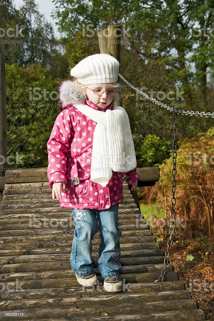 little girl walking over a bridge royalty-free stock photo