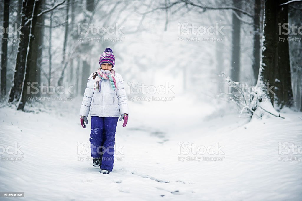 Little girl walking through snowy winter forest stock photo