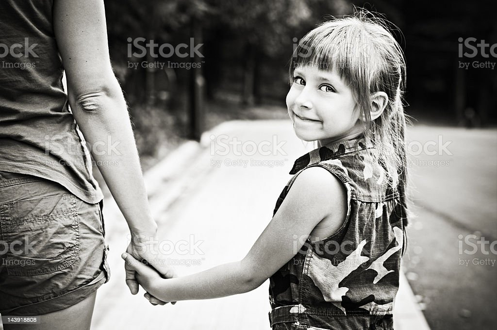 Little girl walking with mommy stock photo