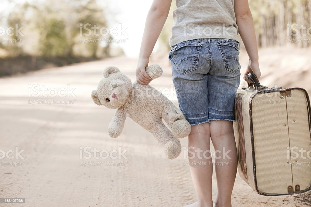 Little Girl Walking with Old Teddy Bear and Suitcase stock photo