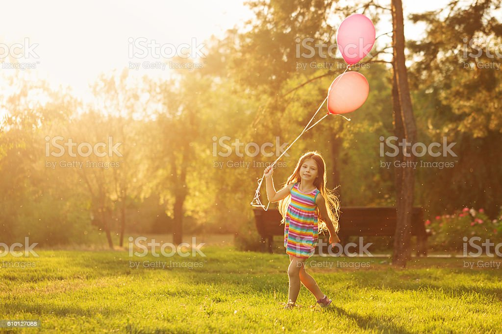 Little girl walks with balloons stock photo