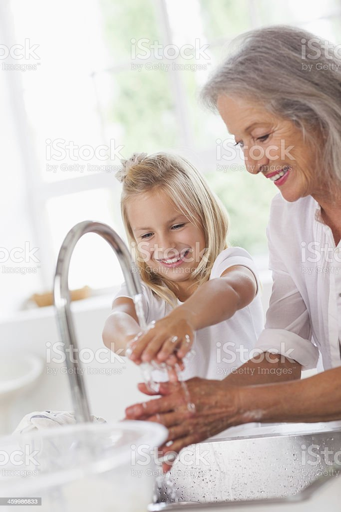 Little girl washing hands with granny stock photo