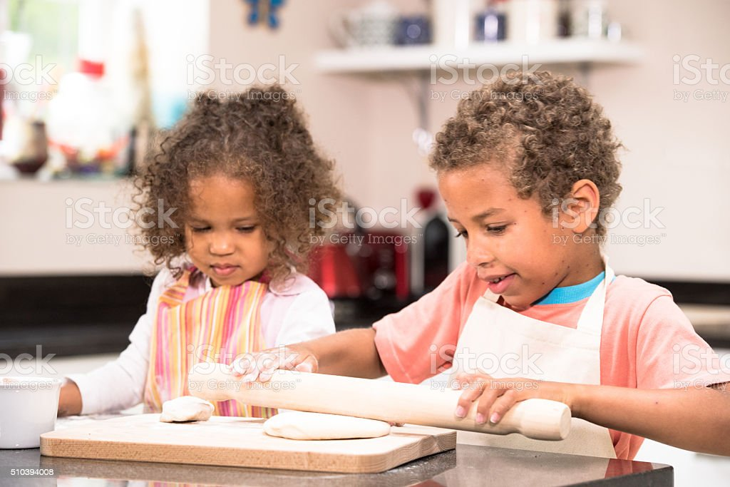 Little Girl Watching Her Brother Prepare Dough stock photo