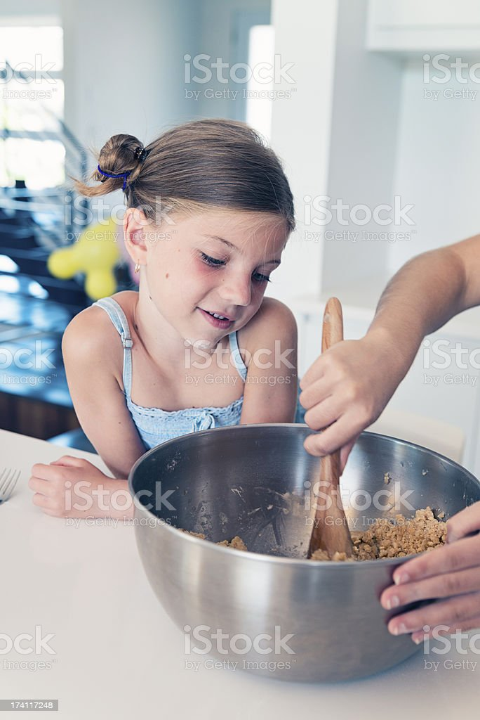 Little girl watching how ingredients mixed together in recipe. royalty-free stock photo