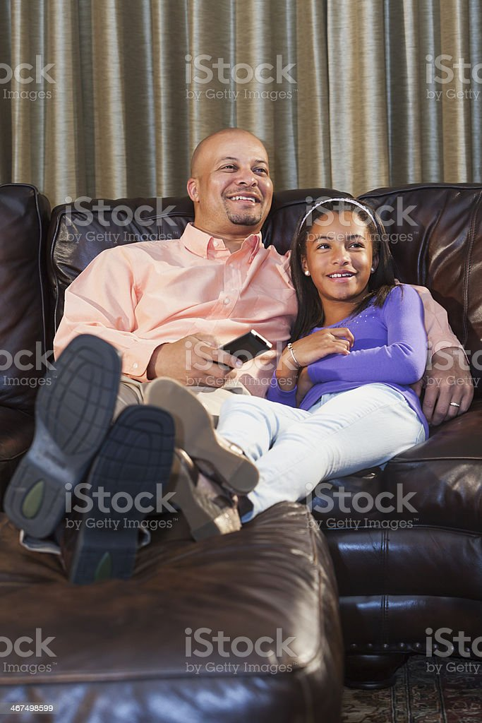 Little girl watching TV with father on couch smiling stock photo