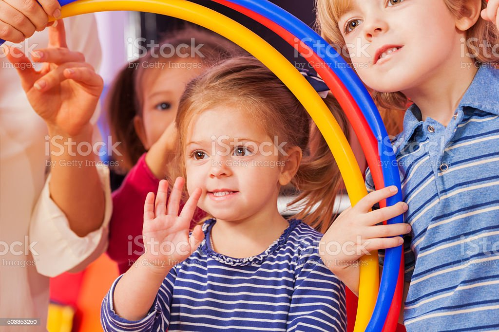 Little girl wave hand looking though hoop stock photo