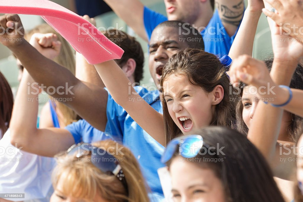 Little girl waving foam finger and cheering in stadium crowd royalty-free stock photo