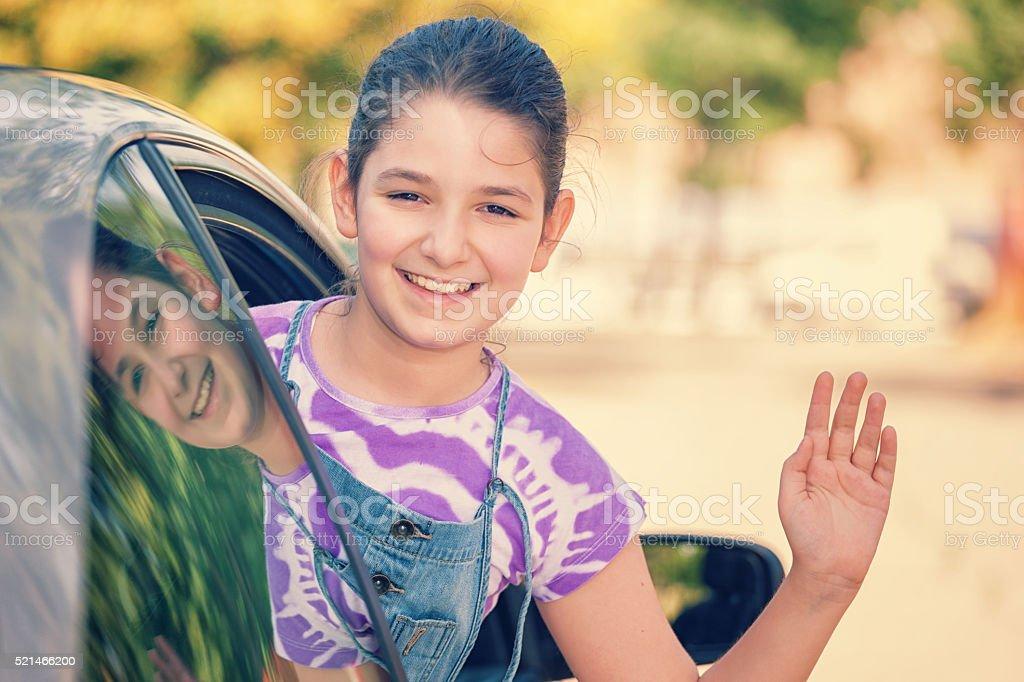 Little Girl Waving From Car Window stock photo