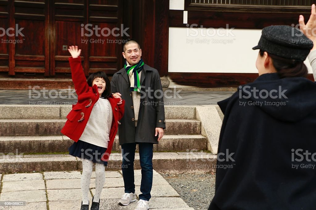 Little girl waving hand to mother stock photo