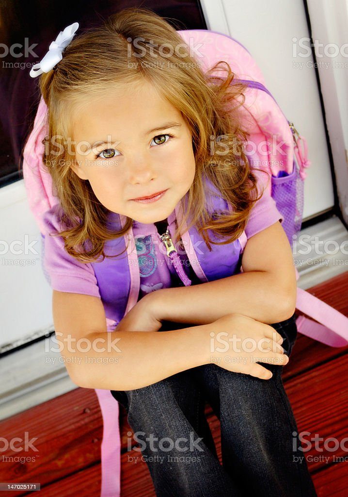 A little girl wearing a backpack on the first school day royalty-free stock photo