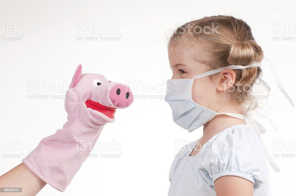 Little girl wearing a protective mask and piggy puppet stock photo