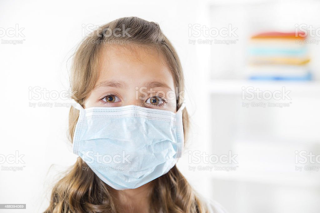 Little girl wearing a protective mask stock photo