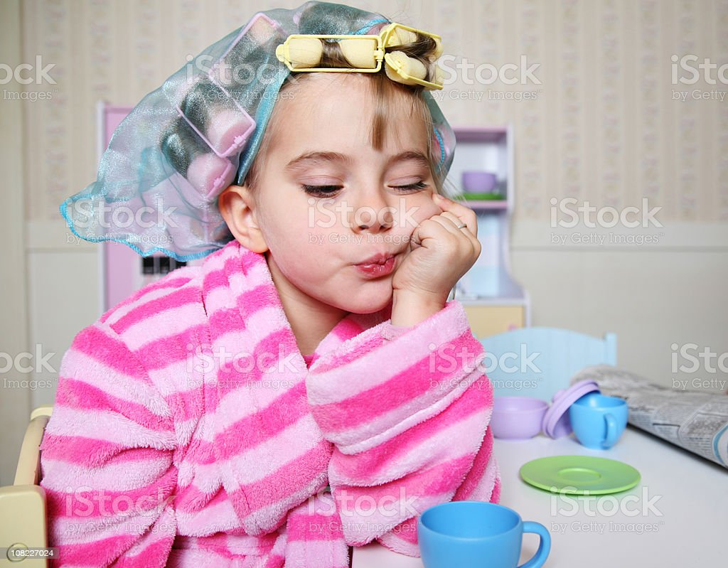 Little Girl Wearing Hair Rollers and Bathrobe at Toy Table stock photo