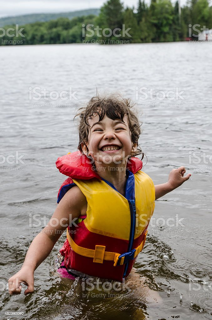 Little girl wearing life vest in lake and smiling stock photo