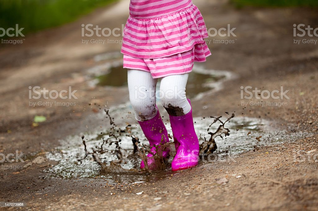 Little girl wearing pink jumping in a puddle stock photo